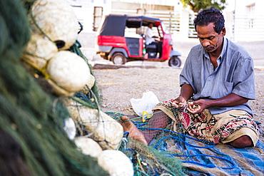Portrait of a fisherman mending his fishing nets in Negombo, West Coast, Sri Lanka, Asia
