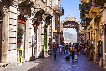 Tourists entering Corso Umberto, the main street in Taormina through the Porta Messina gate, Taormina, Sicily, Italy, Europe