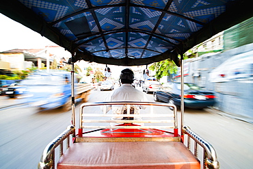 Tuktuk driver speeding along the roads of Phnom Penh, Cambodia, Indochina, Southeast Asia, Asia