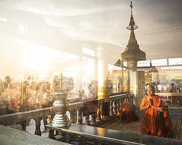 Buddhist Monks praying at Golden Rock Temple (Kyaiktiyo Pagoda) at sunset, Mon State, Myanmar (Burma), Asia