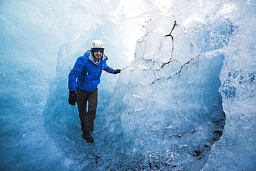 Tourist exploring an ice cave on Breidamerkurjokull Glacier, Vatnajokull Ice Cap, Iceland, Polar Regions