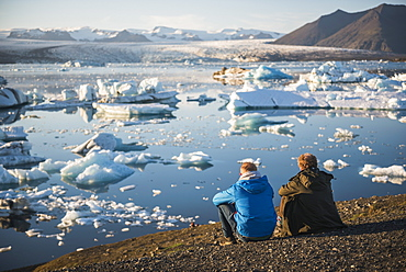 Father and son on holiday at Jokulsarlon Glacier Lagoon at sunset, South East Iceland, Iceland, Polar Regions