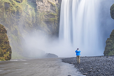 Tourist taking a photo of Skogafoss Waterfall, Skogar, South Region (Sudurland), Iceland, Polar Regions