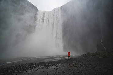 Tourist taking a photo in the spray at Skogafoss Waterfall, Skogar, South Region (Sudurland), Iceland, Polar Regions