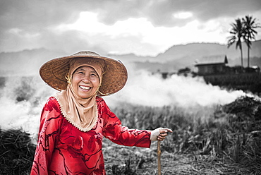 Portrait of a farmer burning crops in rice paddy fields, Bukittinggi, West Sumatra, Indonesia, Southeast Asia, Asia