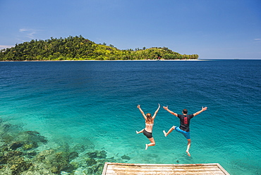 Couple jumping into the Pacific Ocean at Twin Beach, a tropical white sandy beach near Padang in West Sumatra, Indonesia, Southeast Asia, Asia