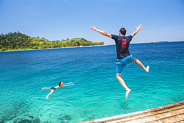 Jumping into the sea and playing in the ocean at Twin Beach, a tropical white sandy beach near Padang in West Sumatra, Indonesia, Southeast Asia, Asia