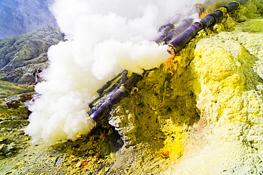 Toxic sulphur fumes escaping from the ceramic pipes at Kawah Ijen, Java, Indonesia, Southeast Asia, Asia