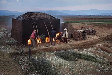 Brick workers firing a kiln near Antsirabe, Vakinankaratra Region, Madagascar, Africa