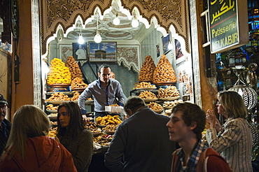 Shop keeper selling sweet cakes to tourists in the souks at night, Marrakech (Marrakesh, Morocco, North Africa, Africa