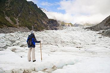 Female tourist walking on Fox Glacier, Westland National Park, UNESCO World Heritage Site, South Island, New Zealand, Pacific