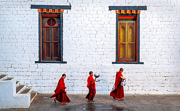 Three Buddhist monks carrying food bowls, Kyichu Temple, Bhutan, Asia