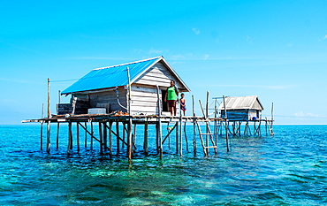 Women and young boy in hut built over the water by Bajau fishermen, who live there for three months, Togian Islands, Indonesia, Southeast Asia, Asia