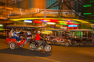 Motion blur image of a tuk-tuk at night in the capital city of Phnom Penh, Cambodia, Indochina, Southeast Asia, Asia