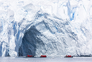 Lindblad Expeditions guests in a Zodiac near an arch in a glacier face in Paradise Bay, Antarctica, Polar Regions