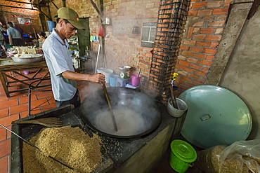 Man making palm sugar rice candy over fire at Cai Be, Vietnam, Indochina, Southeast Asia, Asia