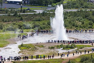 Tourists watch the eruption of the Strokkur geyser, Haukadalur valley, Hvita River, Iceland, Polar Regions