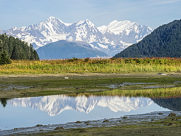The Fairweather Range reflected in calm water, Fern Harbour, Glacier Bay National Park, Alaska, United States of America
