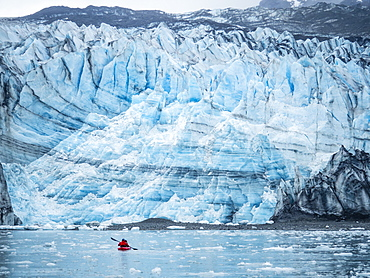 A kayaker paddling in front of Lamplugh Glacier, Glacier Bay National Park and Preserve, UNESCO World Heritage Site, Alaska, United States of America, North America