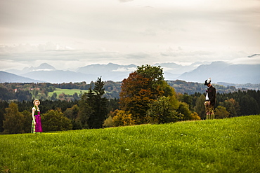 Couple wearing traditional Bavarian costumes standing on a meadow, Bad Toelz, Upper Bavaria, Germany