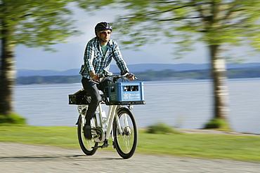 Man cycling with an E-bike along lake Starnberg, Upper Bavaria, Germany