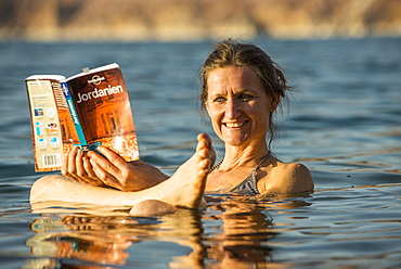Woman reading a guidebook in Dead Sea, Jordan, Middle East