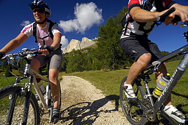 Young couple riding mountain bikes under blue sky, South Tyrol, Italy, Europe