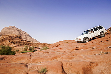 Off-road vehicle downhill driving above a slab of rock, Wadi Rum, Jordan, Middle East
