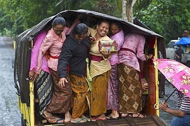 Balinese women squeezing themself on the back of a truck on the way home from a temple visit, Pura Luhur Batu Karu, Bali, Indonesia