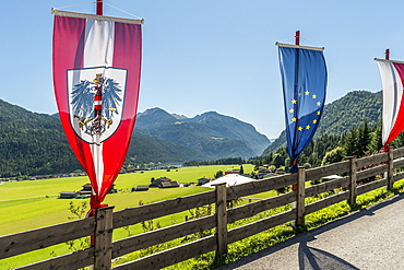 Flags at a fence, lake Achensee and Achenkirch in background, Tyrol, Austria