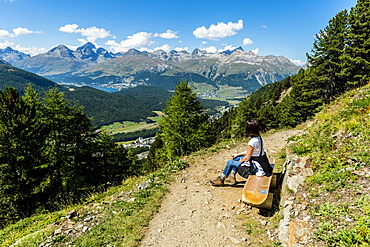 Female hiker resting on a bench, Muottas Muragl, Pontresina, Upper Engadin, Canton of Graubuenden, Switzerland