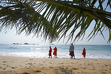 View through palm leaves towards the beach, buddhist novices at the sea, Hikkaduwa, Southwest coast, Sri Lanka