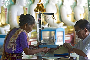 Gold leaf salesperson in Oohmin Thonze pagoda, Sagaing Hill on the banks of Irrawaddy river, 20km from Mandalay, Myanmar, Burma