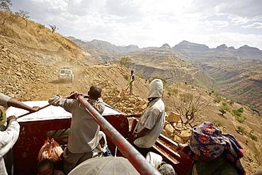 Passengers on the loading area of a truck, road construction zone, near Adi Ar Kay, Amhara region, Ethiopia