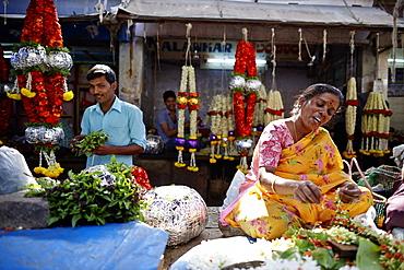 Woman stringing flower garland, Devaraja Market, Mysore, Karnataka, India