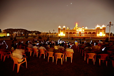 Visitors photographing illuminated Amba Vilas Palace in the evening, Mysore, Karnataka, India