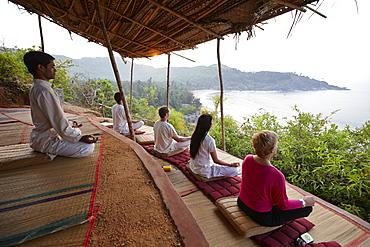 Meditation before sunrise above Om beach, Gokarna, Karnataka, India