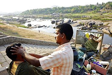 Hairdresser working above the Tungabhadra River, Hampi, Karnataka, India