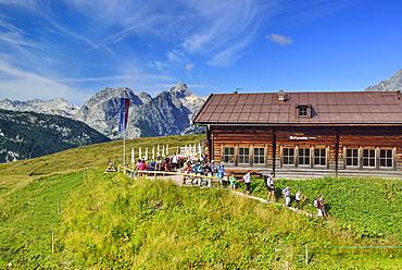 Hikers leaving alpine hut in front of Hundstod, Gotzenalm, Berchtesgaden National Park, Berchtesgaden Alps, Upper Bavaria, Bavaria, Germany