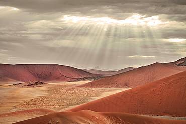 view from Dune 45 to the landscape around Sossusvlei, sun rays breaking through the clouds, Namib Naukluft National Park, Namibia, Namib desert, Africa