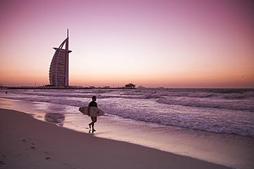 Surfer walking along the beach near Burj al Arab hotel at sunset, Dubai, United Arab Emirates