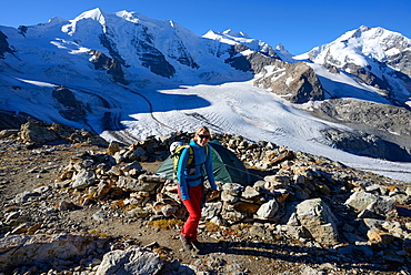 Woman hiking with view to Piz Palue (3905 m), Bellavista (3922 m), Piz Bernina (4049 m) and Pers glacier, Engadin, Grisons, Swit