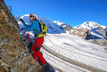 Woman climbing the via ferrata at Piz Trovat with view to Piz Palue (3905 m), Bellavista (3922 m), Piz Bernina (4049 m), and Per