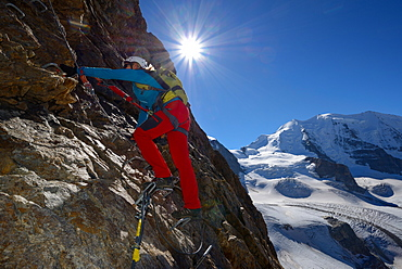 Woman climbing the via ferrata at Piz Trovat with view to Piz Palue (3905 m) and Pers glacier, Engadin, Grisons, Switzerland