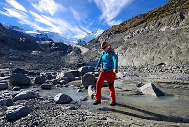 Woman crossing the Morteratsch Creek near the glacier mouth of Morteratsch glacier with view to Bellavista (3922 m), Piz Bernina