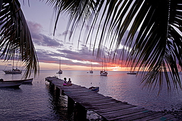 Children sitting on a wooden jetty at the sea in sunset, Dominica, Lesser Antilles, Caribbean