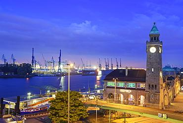 Illuminated St. Pauli-Landungsbruecken with Pegelturm and harbour in background, Landungsbruecken, Hamburg, Germany