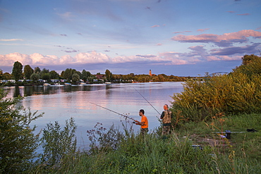 Two fishermen on the banks of the Main river with camp site at sunset, Volkach, Franconia, Bavaria, Germany