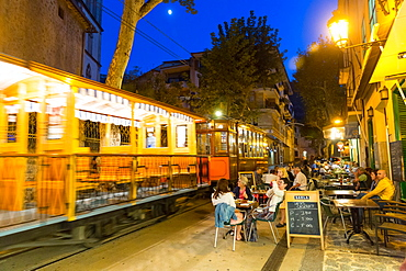 historical tram driving between Port de Soller and Palma de Mallorca in the evening, guests in restaurants, Serra de Tramuntana, Soller, Majorca, Balearic Islands, Spain, Europe