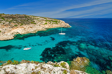 A sailing yacht and a fishing boat anchored in a lonely bay with clear blue water, Mallorca, Balearic Islands, Spain, Europe